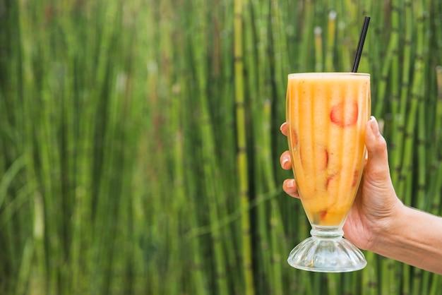 Mano con vaso de batido cerca de bambú Foto gratis