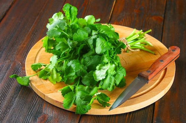 Manojo de cilantro fresco en los tableros, hierbas frescas en la mesa de madera. Foto Premium