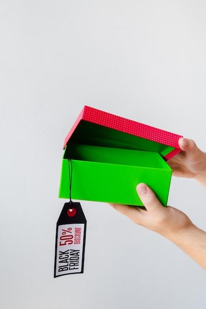 Manos abriendo regalo de viernes negro con etiqueta Foto gratis