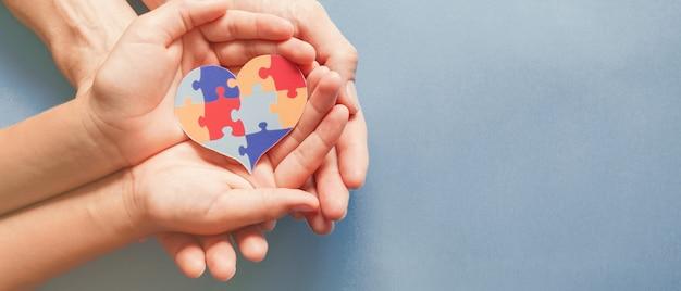 Manos de adultos y niños con rompecabezas en forma de corazón, conciencia del autismo, concepto de apoyo familiar del espectro autista, día mundial de la concienciación sobre el autismo Foto Premium