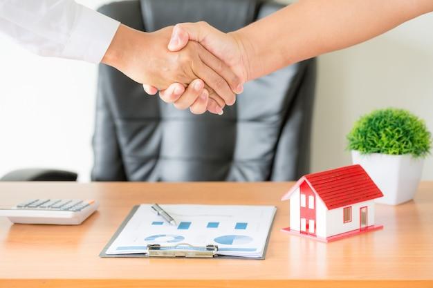 Manos del agente y del cliente estrechándose la mano después de firmar un contrato, comprar un apartamento nuevo Foto gratis