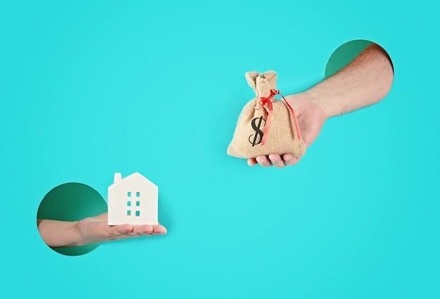 Manos en los agujeros de papel que sostienen la casa y una bolsa con dinero. Foto Premium