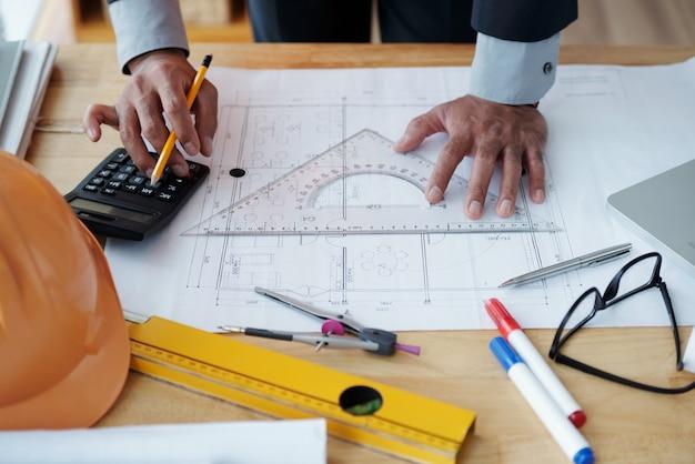 Manos de arquitecto masculino irreconocible trabajando en dibujo técnico y usando calculadora Foto gratis