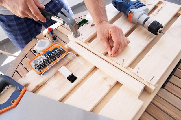 Manos clavando clavo con martillo en estante de madera Foto gratis
