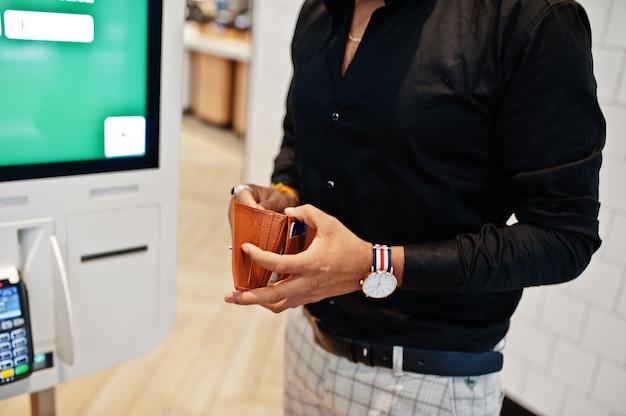 Las manos del cliente del hombre en la tienda hacen pedidos y pagan a través del quiosco de piso de pago propio para comida rápida, terminal de pago. su cartera y encontrar la tarjeta de crédito. Foto Premium