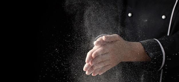 Manos del cocinero en harina en bandera negra del fondo. Foto Premium