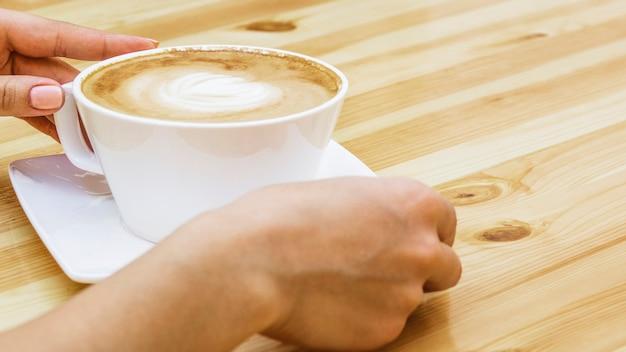Manos cogiendo taza de café Foto gratis