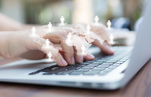 Manos con ordenador portátil y mapa del mundo virtual Foto Gratis