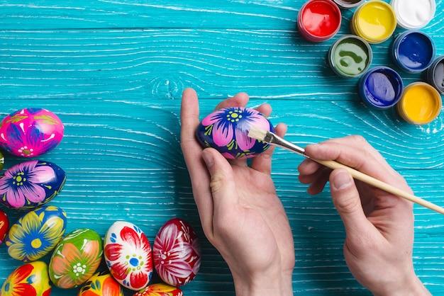 pincel pintando. manos con un pincel pintando huevo de pascua foto gratis d