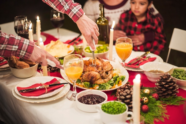 Manos cortando pavo en la cena de navidad Foto gratis