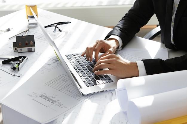 Manos del director ejecutivo de la empresa constructora en traje negro escribiendo mensajes por correo electrónico a socios en la computadora portátil con dibujos, sello, divisor en la mesa. Foto gratis