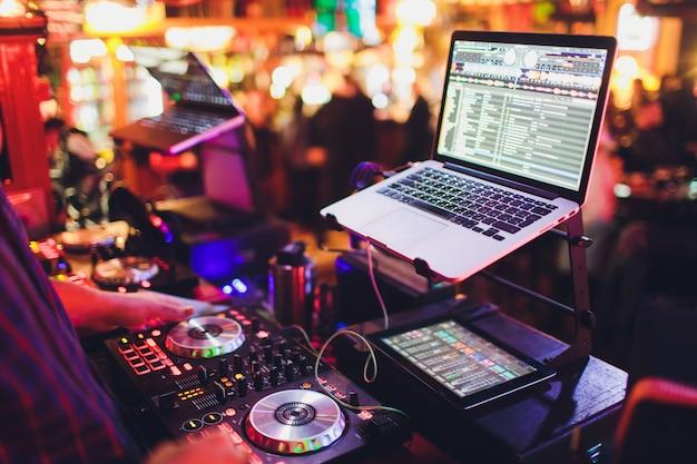Manos de dj mezclan pistas en un tocadiscos digital y software en una computadora portátil con software de mezcla profesional Foto Premium