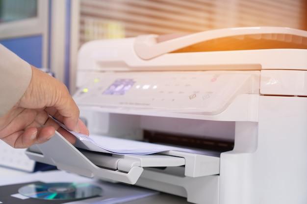 Manos de la empresaria que trabajan en el proceso de prensa de papel en impresora láser en el escritorio de trabajo ocupado Foto Premium