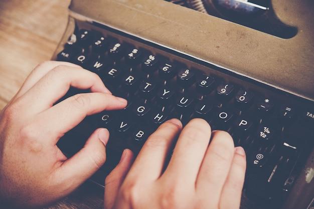 Manos escribiendo en máquina de escribir vintage en mesa de madera. Foto gratis