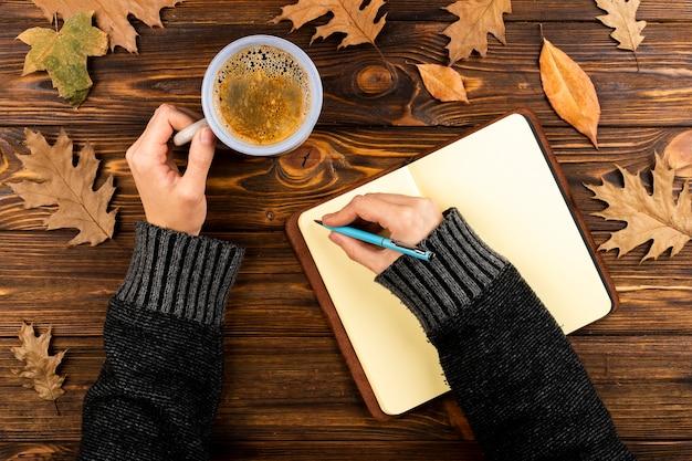 Manos escribiendo en la vista superior del cuaderno Foto gratis