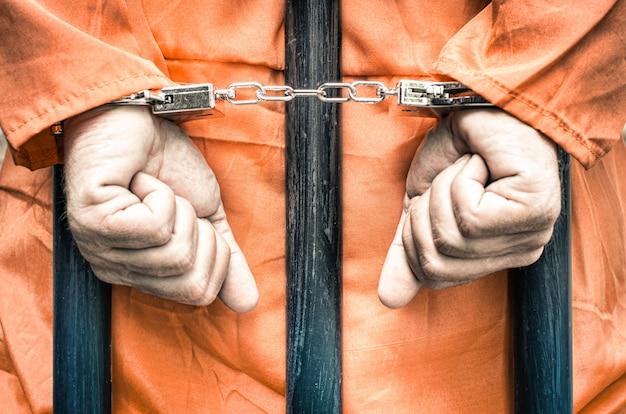 Las manos esposadas de un prisionero tras las rejas de una prisión con ropa naranja Foto Premium
