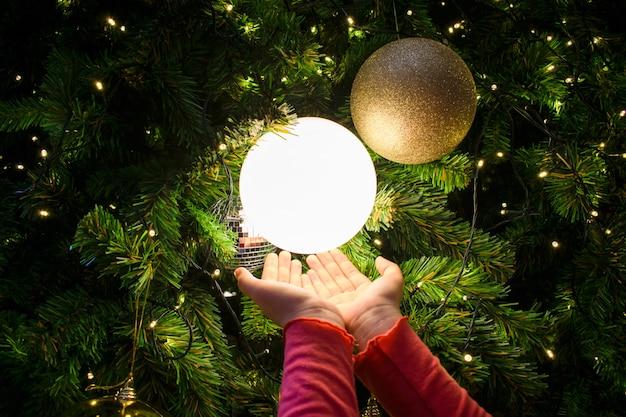 Manos femeninas con una bola de luz. árbol de navidad decorado en plata y oro. Foto Premium