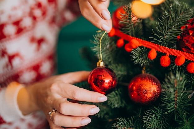 Manos femeninas de cerca, decorando el árbol de navidad con bolas rojas Foto gratis