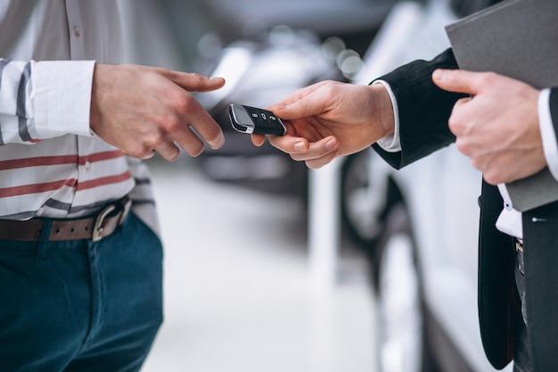 Las manos femeninas se cierran para arriba con llaves del coche Foto gratis