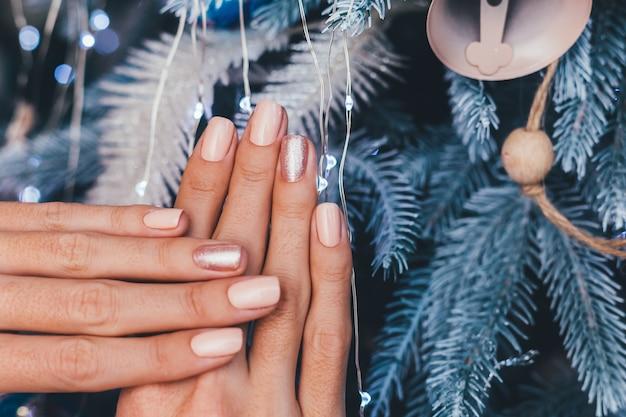 Manos femeninas con diseño de uñas de año nuevo de navidad. manicura de esmalte de uñas beige nude, un dedo bronce dorado brillante Foto gratis