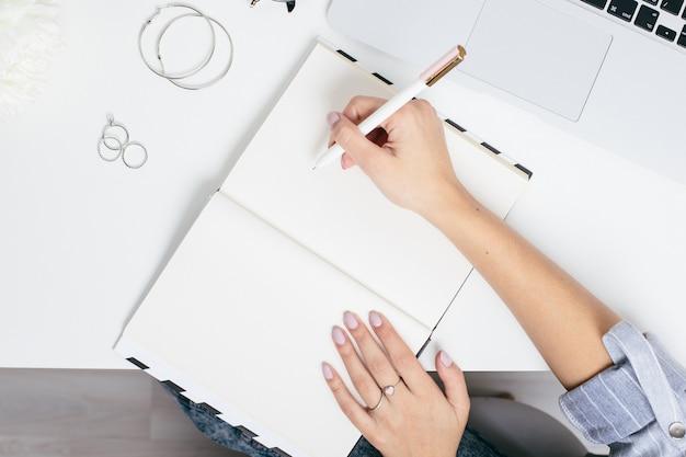 Manos femeninas haciendo notas en un bloc de notas sobre una mesa blanca con un teclado portátil Foto Premium