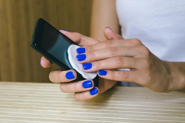 Manos femeninas limpian el polvo de la pantalla táctil del teléfono móvil Foto Premium