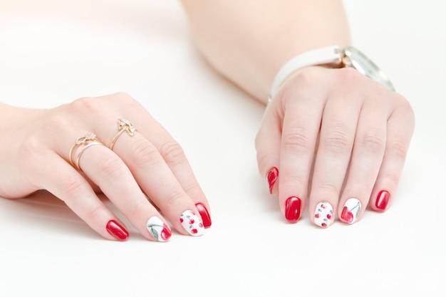 Manos femeninas con manicura, esmalte de uñas rojo, dibujo con cerezas. fondo blanco. Foto Premium