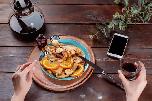 Manos femeninas y panqueques con jugo. desayuno saludable Foto gratis