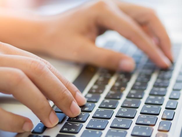 Manos femeninas del primer que pulsan en el teclado de la
