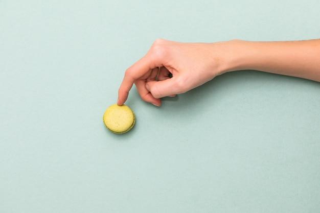 Manos femeninas que tocan la torta verde de los macarrones. vista superior, endecha plana. copyspace Foto Premium