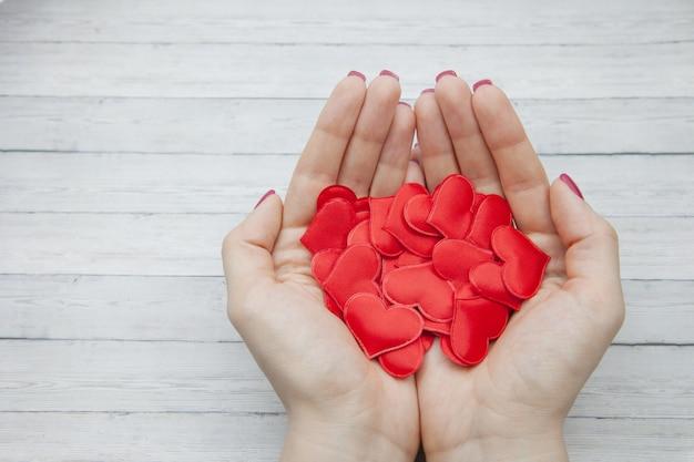 Las manos femeninas sostienen muchos corazones rojos en la palma en un fondo de madera, concepto de salvar amor Foto Premium