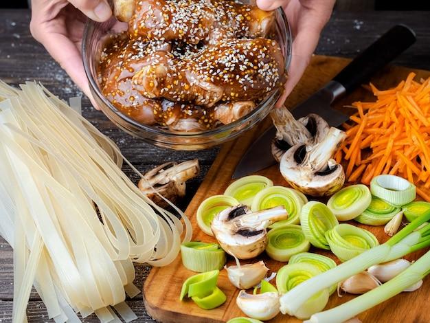 Manos femeninas sostienen un plato de pollo con salsa teriyaki y semillas de sésamo Foto gratis