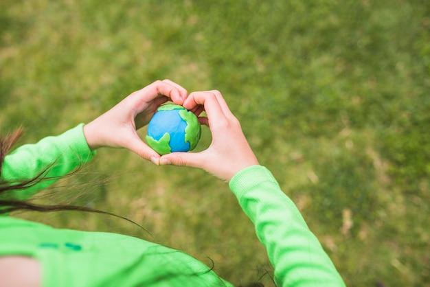 Manos en forma de corazón rodean el colorido planeta plastilina. Foto gratis