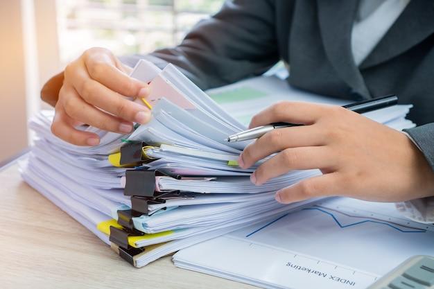 Manos gerentes de negocios mujeres jóvenes comprobando la disposición de la pila de documentos sin terminar Foto Premium