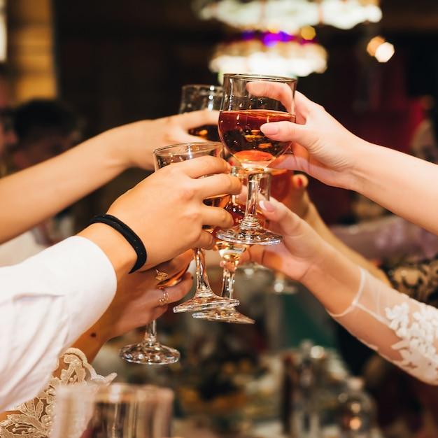 Manos de un grupo de personas tintineando y tostando copas de vino tinto en una fiesta festiva en un restaurante Foto Premium