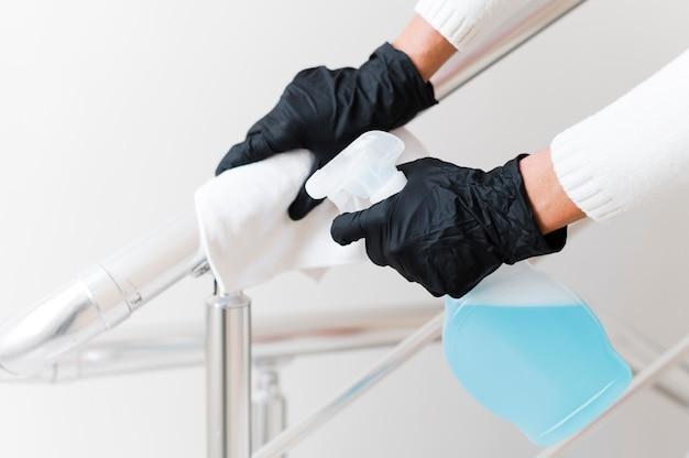Manos con guantes desinfectando pasamanos Foto Premium