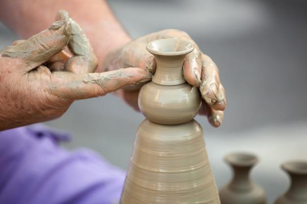 Manos haciendo cerámica en una rueda Foto Premium