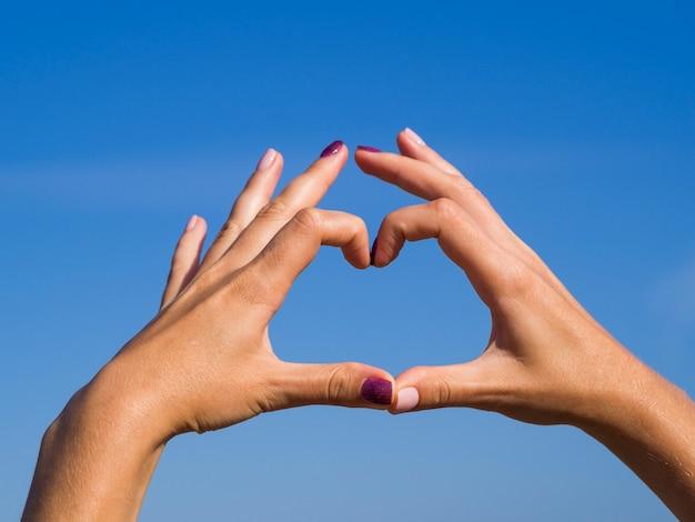Manos haciendo forma de corazón en el cielo Foto gratis