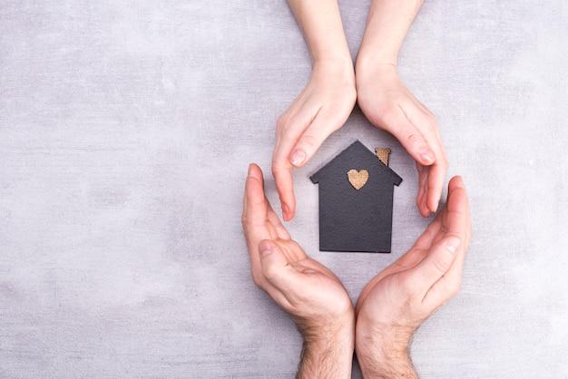 Las manos del hombre y la mujer rodean un modelo de una casa oscura. concepto de bienes raíces y seguros, vista plana, vista superior Foto Premium