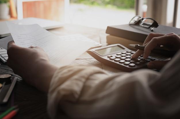 Manos de hombre de negocios con libreta de cuenta de ahorro con calculadora, cuenta y concepto de ahorro. Foto Premium