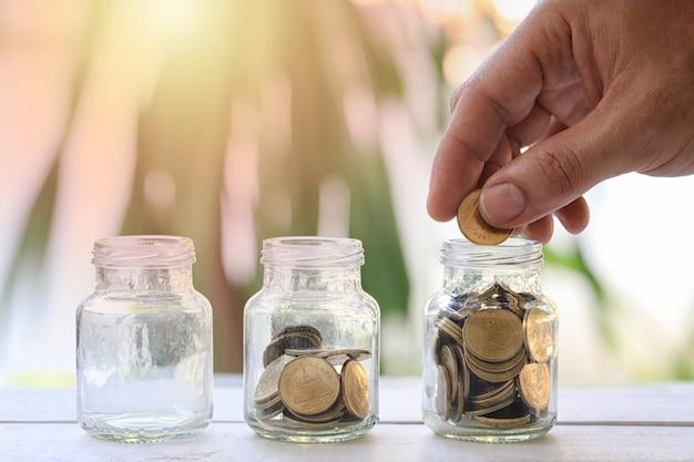 Las manos del hombre de negocios ponen un dinero en la botella de cristal y tienen moneda de oro. Foto Premium