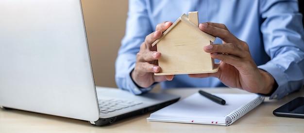 Manos del hombre de negocios que llevan a cabo el modelo de madera de la casa. Foto Premium