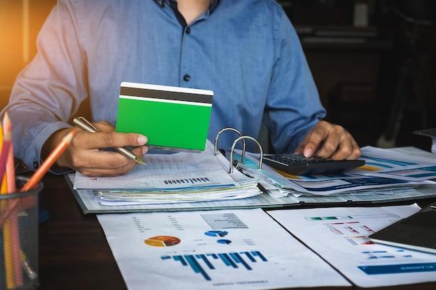 Manos de hombre de negocios sosteniendo la libreta de ahorro con la calculadora Foto Premium