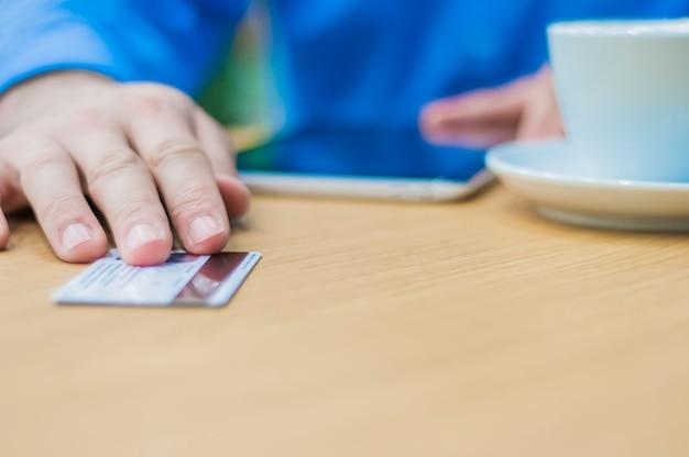 Manos del hombre que da la tarjeta plástica al camarero para pagar la orden. hombre de negocios que paga con una tarjeta de crédito o débito Foto gratis