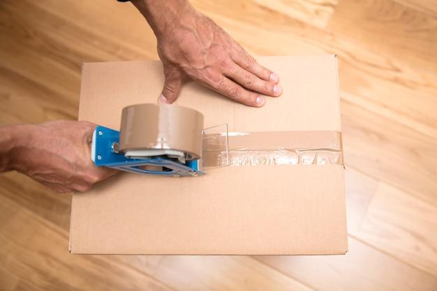 Manos de un hombre que usa un dispensador de cinta para sellar una caja de envío Foto Premium