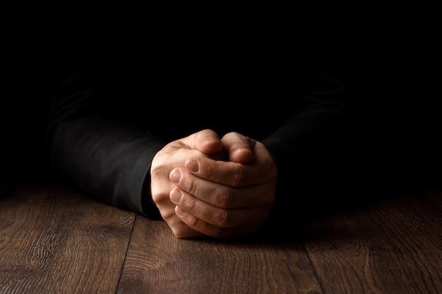 Manos de hombres en oración Foto Premium