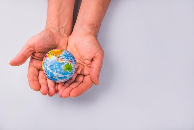Manos humanas que sostienen el globo contra el fondo blanco Foto gratis