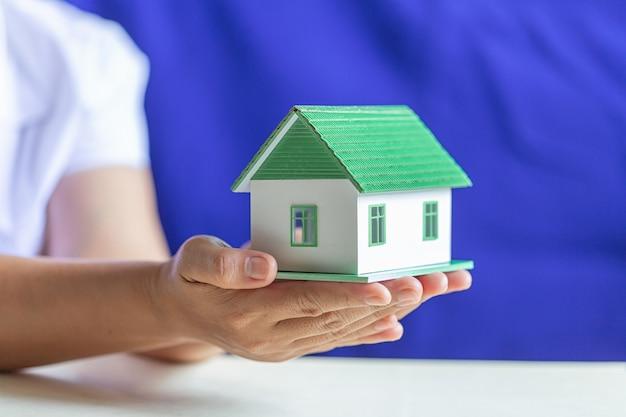 Manos humanas sosteniendo modelo de casa de ensueño. Foto gratis