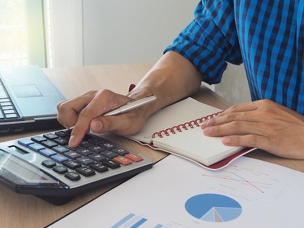 Manos humanas usando una calculadora Foto Premium