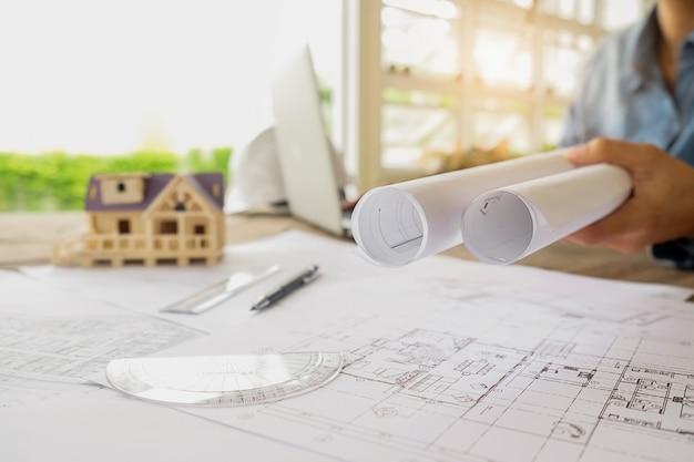 Manos del ingeniero que trabajan en blueprint, concepto de la construcción. herramientas de ingeniería.vintage efecto de filtro retro tono, enfoque suave (enfoque selectivo) Foto gratis